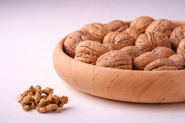 皮をむいたナッツ、アングルビュー、健康食品の概念に近い白い背景の上の木製のボウルにクルミヒープ食品