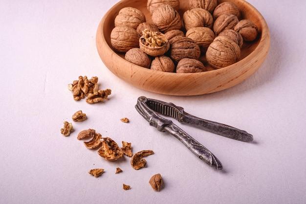 Еда кучи грецких орехов в деревянной миске с половиной очищенной гайки, треснутой ореховой скорлупой, рядом с винтажным щелкунчиком на белом фоне, угол обзора, концепция здорового питания