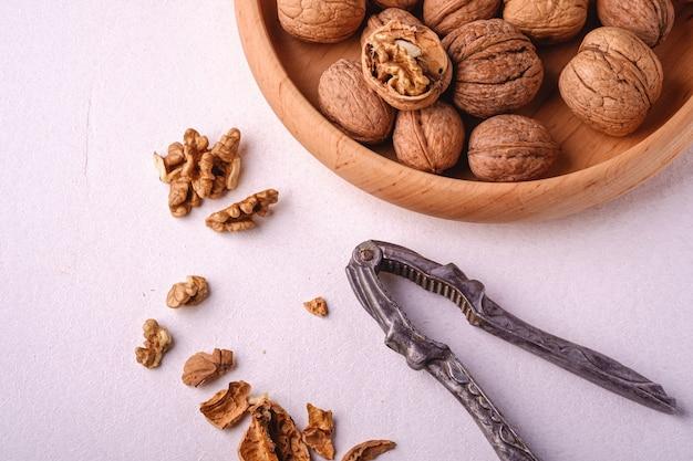 半分皮をむいたナッツ、ひびの入った殻、白い背景、視野角、健康食品の概念にビンテージくるみ割り人形の近くで木製ボウルにクルミヒープ食品