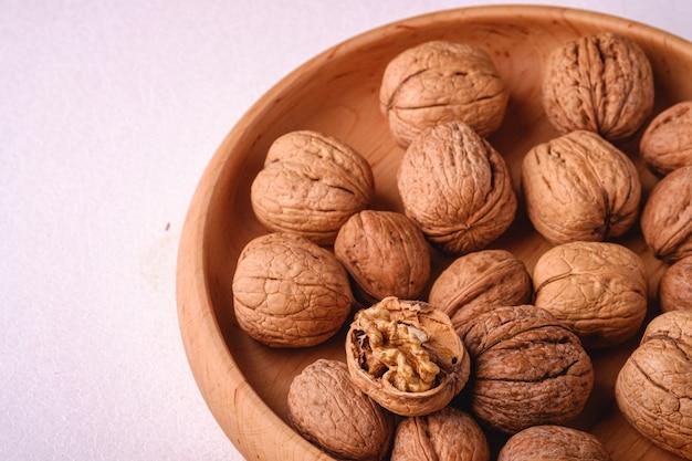 Грецкие орехи кучи пищи в деревянной миске на белом фоне с половиной очищенной гайки, угол зрения, концепция здорового питания
