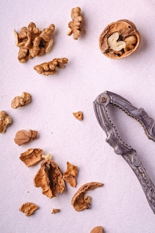 Еда кучи грецких орехов с половиной очищенной гайки, треснутой скорлупы, рядом с винтажным щелкунчиком на белом фоне, вид сверху, концепция здорового питания