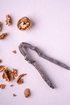 白い背景、上面、健康食品のコンセプトにヴィンテージくるみ割り人形の近くに半分皮をむいたナッツ、ひびの入ったナッツ殻とクルミのヒープ食品