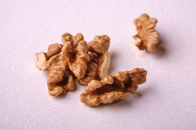 Слезли грецкие орехи наваливают еду на белой предпосылке, взгляде угла, селективном фокусе, концепции здоровой еды