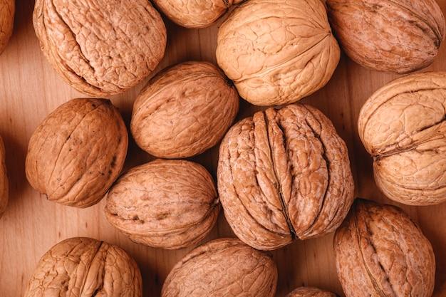 Грецкие орехи кучи пищи в деревянной миске, вид сверху, концепция здорового питания