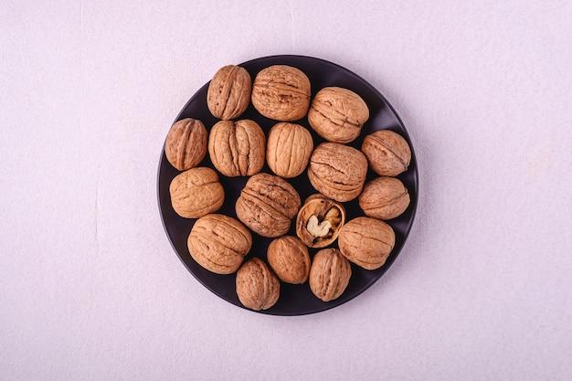 Еда кучи грецких орехов в черной плите с половинной, который слезли гайкой на белой предпосылке, взгляд сверху, концепции здоровой еды