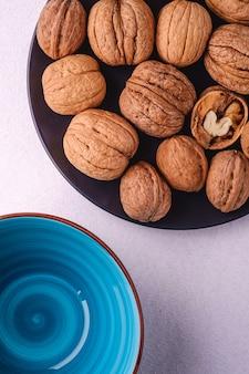 白い背景、上面、健康食品の概念に空の青いボウルの近くに黒いプレートに半分皮をむいたナッツとクルミのヒープ食品