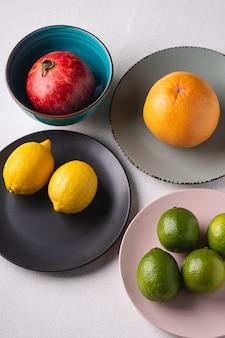 ライム、レモン、グレープフルーツ、白地にカラフルなプレートでザクロ