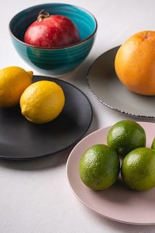 Лайм, лимон, грейпфрут и гранат в красочных тарелках на белом