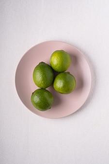 Лайм кислые фрукты в розовой тарелке на белом