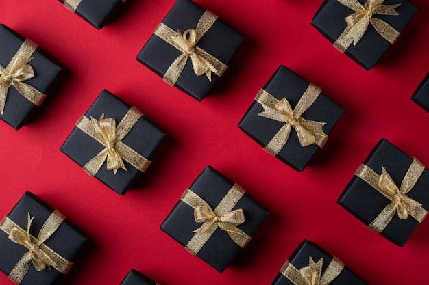 赤い紙の表面、パターン、テクスチャ、分離、トップビュー、フラットレイアウトに金色のリボンと黒のギフトボックス