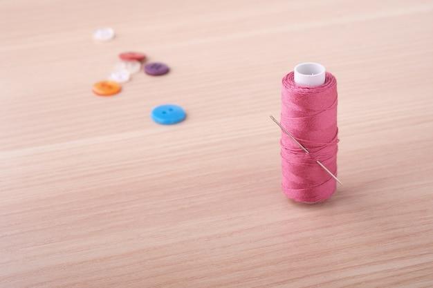 ボタンと針でピンクのスレッドコイルの角度ビューをクローズアップ