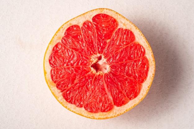 グレープフルーツ半分マクロ、熱帯の創造的な最小限の食品フルーツコンセプト、白い背景、鮮やかな色、トップビューの選択と集中