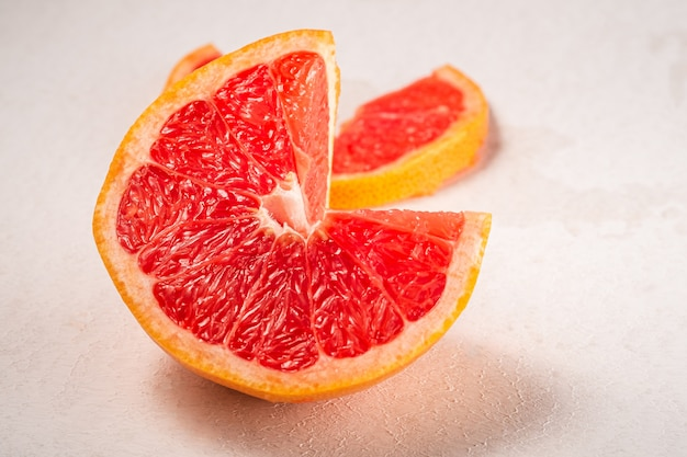 グレープフルーツは、マクロ、白い背景、鮮やかな色、角度の選択と集中に、熱帯の創造的な最小限の食品フルーツコンセプトをカット