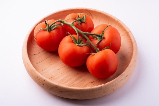 白で隔離される木製のプレートにトマト野菜