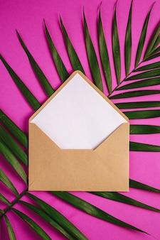 手のひらに白い空のカード、ピンクパープルバックグラウンド、モックアップの空白の手紙と茶色のクラフト紙封筒