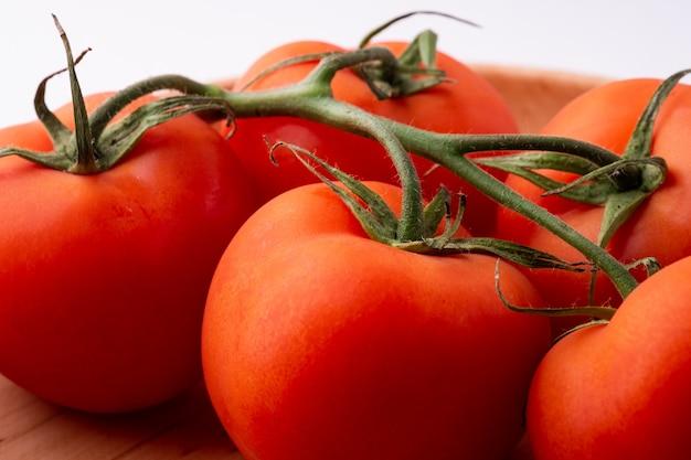 白で隔離される木製のプレートにトマト野菜をクローズアップ