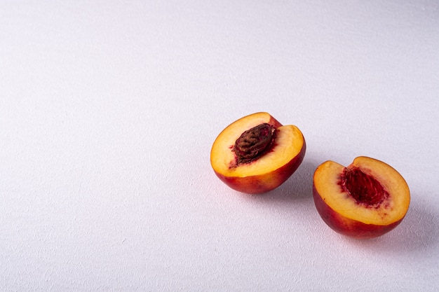 Два ломтика персика нектарин фрукты с семенами на белом