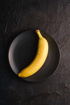 Одиночный плодоовощ банана в черной плите на темной текстурированной предпосылке, взгляд сверху