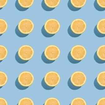レモンの柑橘系の果物のシームレスパターン青の最小限の背景、新鮮なジューシーなトロピカルスライス