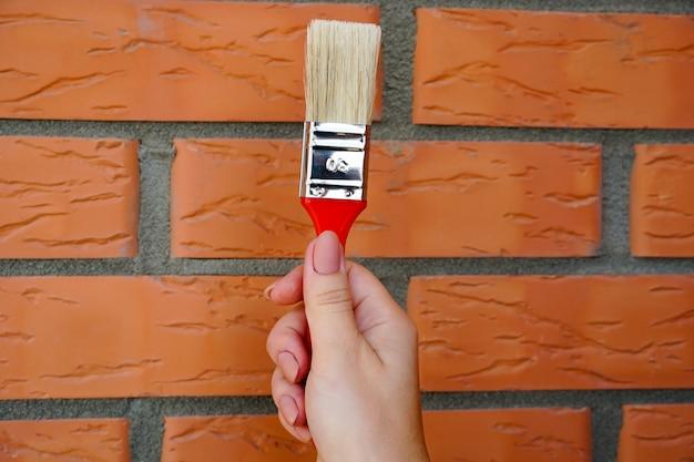 レンガの壁に女の子の手で壁を塗るためのブラシ