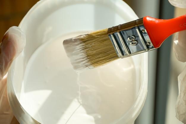 Девушка держит кисть с красной ручкой в руке и собирается покрасить перила балкона белой краской