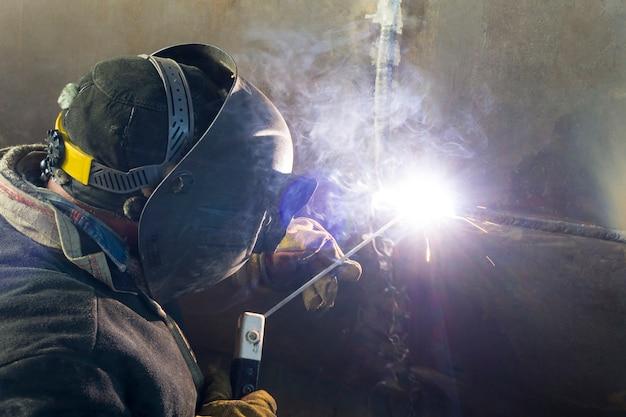 Сварка корпуса теплообменника. сварщик сваривает технологические трубопроводы с ручной дуговой сваркой для нефтеперерабатывающего завода в россии. сварное соединение.