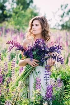 フィールドにルピナスの花束を持つ少女