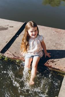 水に足を浸し、笑っている少女