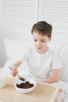 Милый мальчик ест завтрак шоколадные шарики, сидя в постели с белым постельным бельем