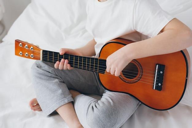 Мальчик играет на маленькой гитаре, сидя на кровати
