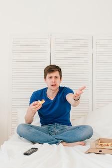 Человек смотрит телевизор, сидя на кровати и ест пиццу