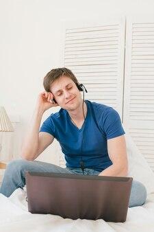 ノートパソコンで音楽を聞いている男性