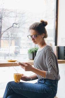 スマートフォンで音楽を聴くとコーヒーを飲む女の子