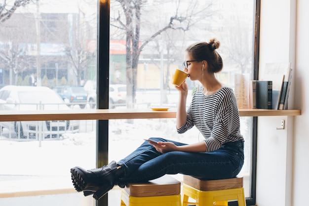 Девушка слушает музыку на вашем смартфоне и пьет кофе