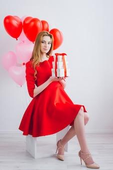 赤いドレスの女の子はギフトボックスを保持します