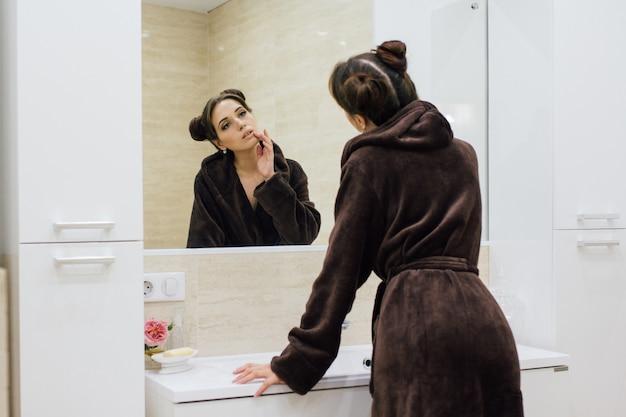 バスルームに茶色の居心地の良いバスローブの女性