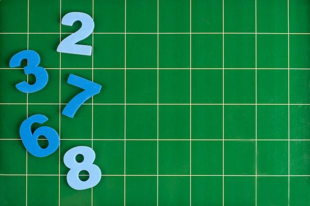 Разные цифры лежат на зеленой поверхности доски
