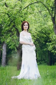 夏の庭の長い白いドレスを着た女性