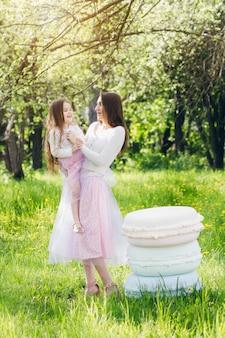 Мама и дочка гуляют весной, цветут яблони