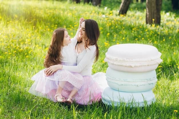 母と幼い娘が春咲くリンゴを歩く