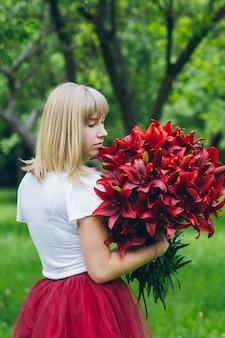 紫色のユリの大きな花束を持つ少女