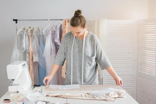 若い女性の裁縫師は服を切る服を作る