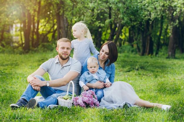 Семья с двумя детьми отдыхает в летнем саду