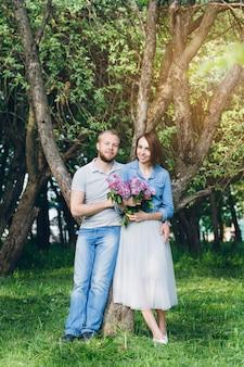 Влюбленная пара отдыхает летом в яблоневом саду