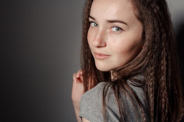 Портрет молодой красивой девушки брюнетки в студии