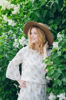 春にライラックの花を持つ金髪の女性