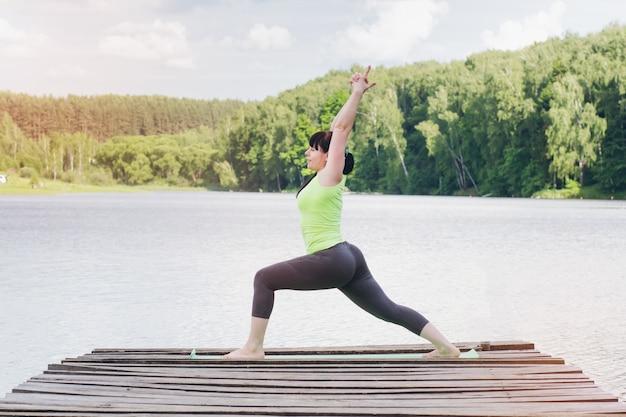 Женщина занимается йогой на мосту летом