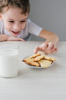 焼きたての自家製クッキーのプレートから子供が盗む
