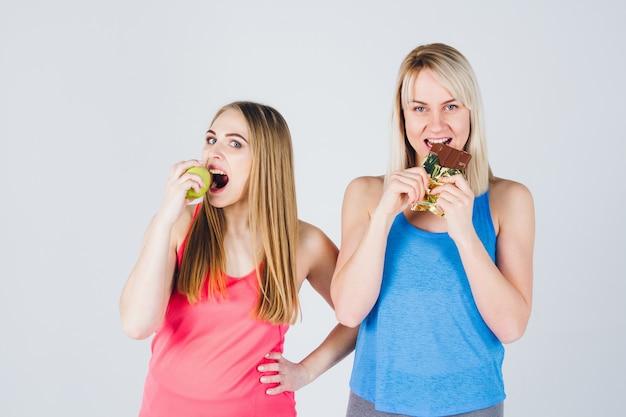 妊娠中の女の子と彼女の友人はリンゴとチョコレートを食べる
