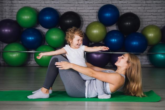 母親と赤ちゃんの女の子がジムで一緒に演習を行う